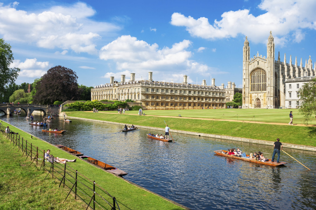 Cambridge, Cambridgeshire, United Kingdom - June 24, 2006: Tourists on punt trip (sightseeing with boat) along River Cam near Kings College in the city of Cambridge, United Kingdom